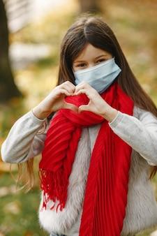 가 공원에 서있는 아이. 코로나 바이러스 테마. 빨간 스카프에 소녀입니다.