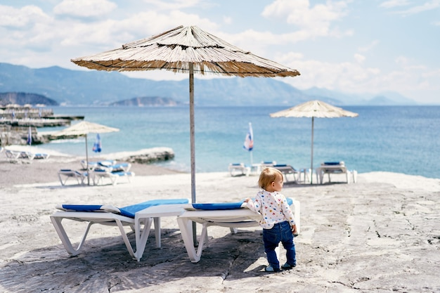 Child stands near a sun lounger on the beach and looks to the side back view