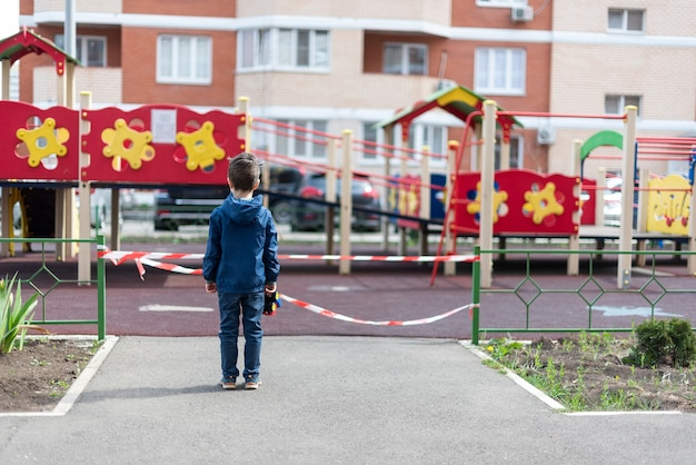 A child stands over a playground fenced with red ribbon holds a toy car in his hand