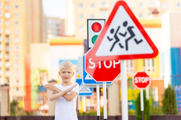 A child stands at a stop sign and holds his hands in a cross