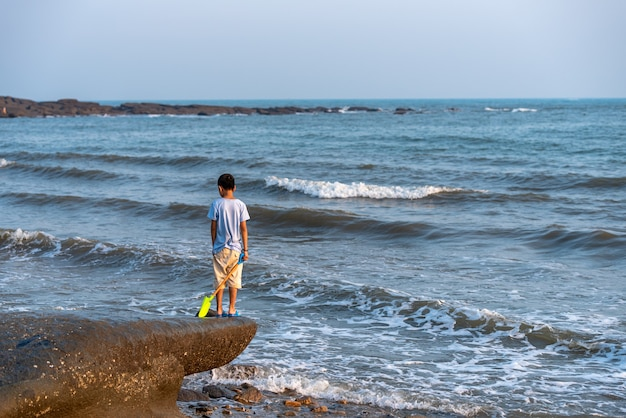 A child stood on a rock by the sea with an iron toy.