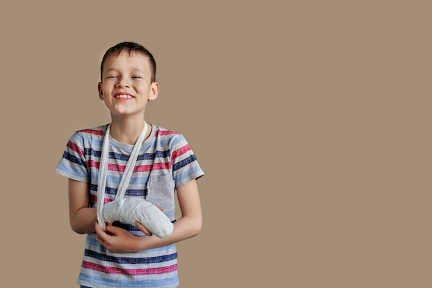 A child in a striped t-shirt with a bandage wrapped around his arm. arm injury.