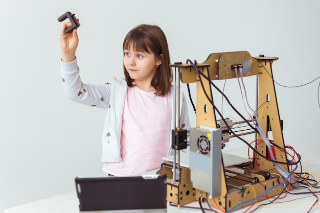 Child student makes the item on the 3d printer. school, technologies and science concept.