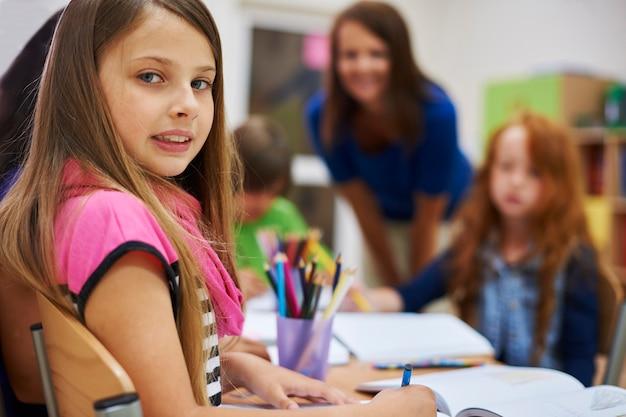 Studente bambino seduto alla sua scrivania