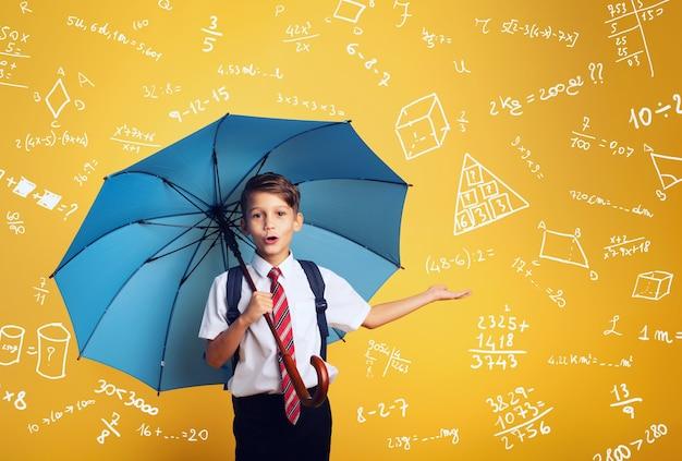 파란 우산을 가진 어린이 학생은 비로부터 자신을 덮습니다. 대수학 연습을 많이합니다.