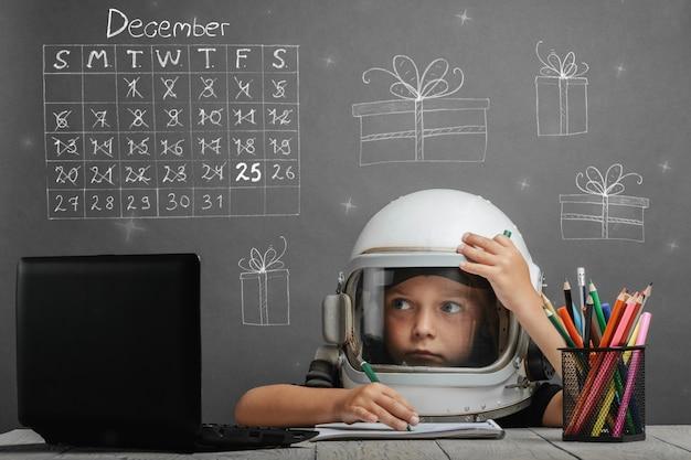 어린이는 우주 비행사의 헬멧을 쓰고 학교에서 원격으로 공부합니다. 크리스마스 개념