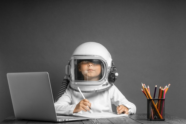 The child studies remotely at school, wearing an astronaut's helmet. back to school