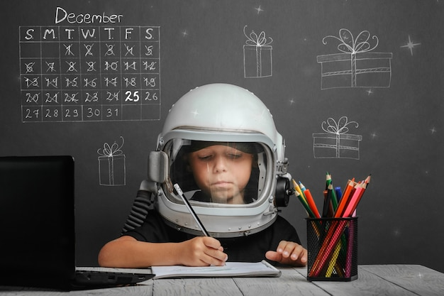 The child studies remotely at school wearing an astronauts helmet