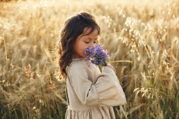 Child in a summer field. little girl in a cute brown dress.
