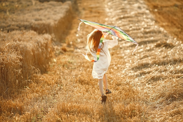 Child in a summer field. little girl in a cute white dress. child with a kite.