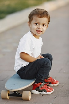 Child in a summer park. boy in a white t-shirt. kid with skate.