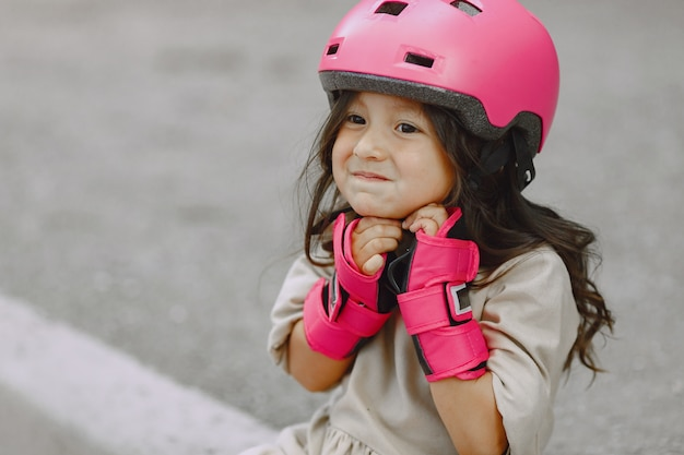 Child in a summer park. kid in a pink helmet. little girl with a roller.