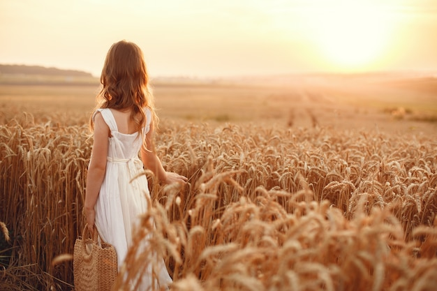 Child in a summer wheat field. little girl in a cute white dress.