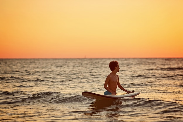 Child surfing on tropical beach. summer vacation in asia. kids swim in ocean water