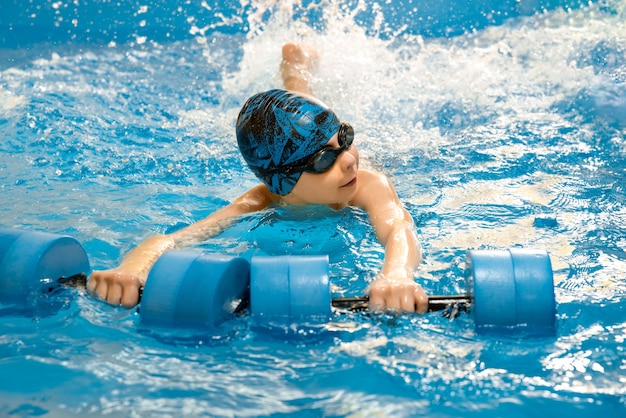 Child swimming with a water dumbbells in hand in swimming pool