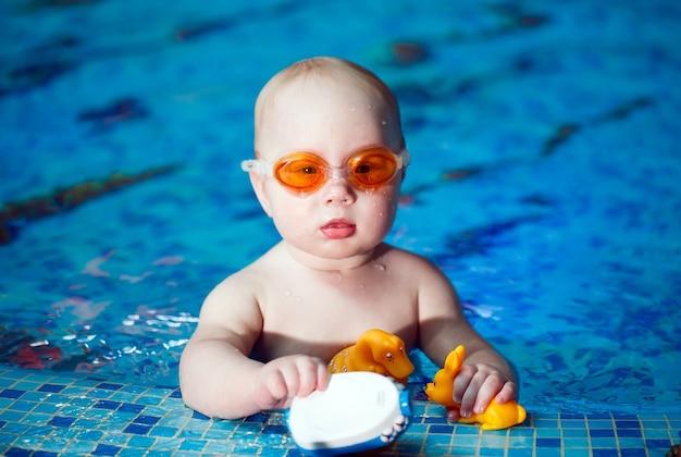 子供はプールで泳ぐ