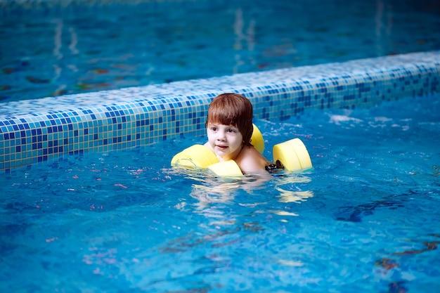 子供はプールで泳ぎます。
