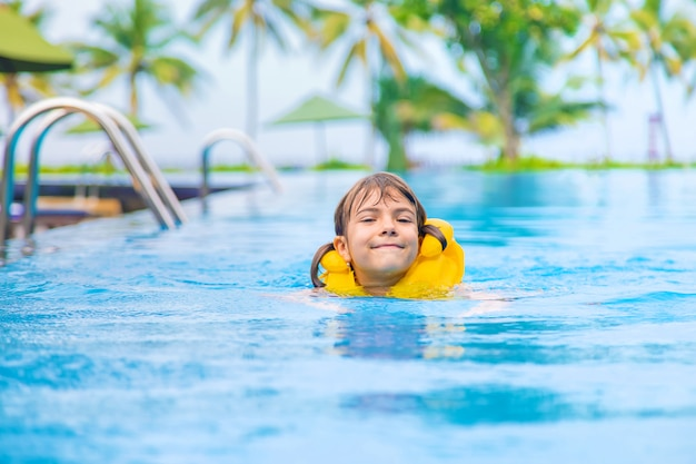 The child swims in the pool in the summer.