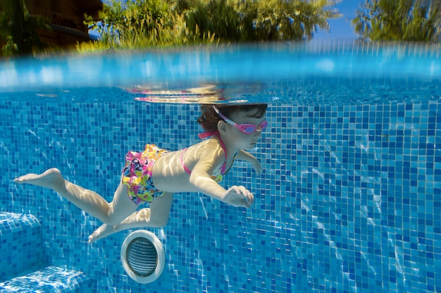 Child swims in pool underwater