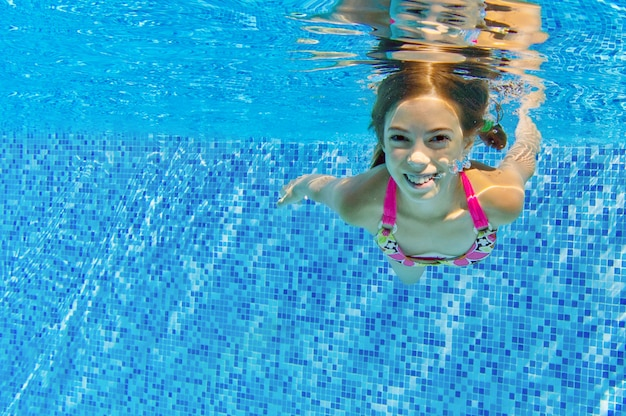 Child swims in pool underwater