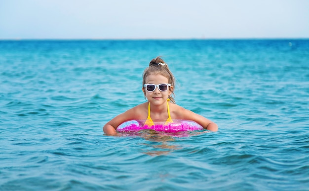 The child swims in a rubber ring in the sea