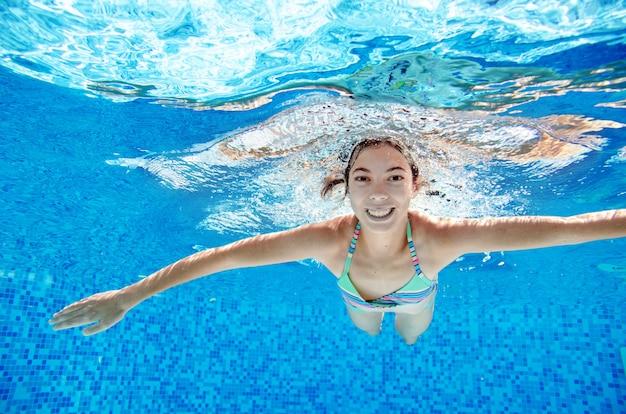 Ребенок плавает под водой в бассейне, веселый активный подросток девушка погружается и веселится под водой, детский фитнес и спорт на семейный отдых на курорте