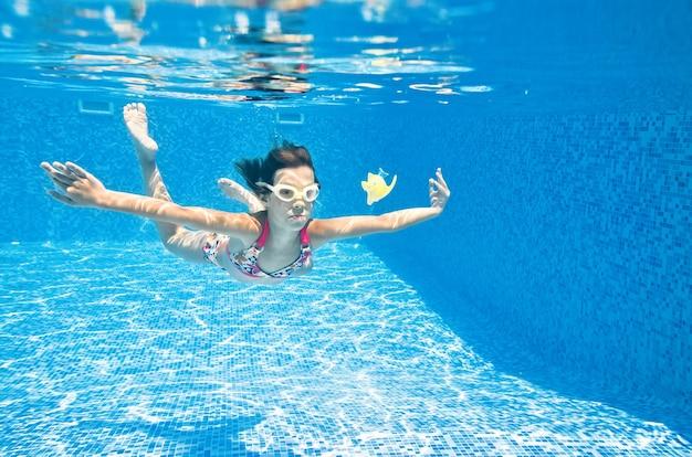 子供はプールで水中を泳ぐ