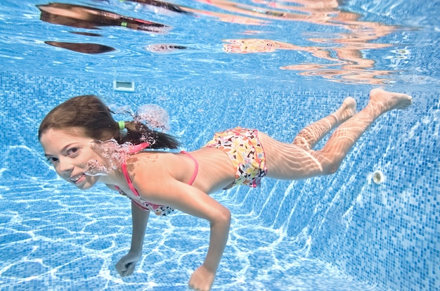 Child swims underwater in swimming pool, active girl dives and has fun under water, kid fitness and sport on family vacation