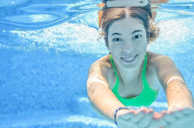 Child swims underwater in swimming pool, happy active teenager girl dives and has fun under water, kid fitness and sport on family vacation on resort