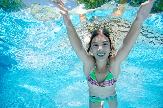 Child swims underwater in swimming pool, happy active teenager girl dives and has fun under water