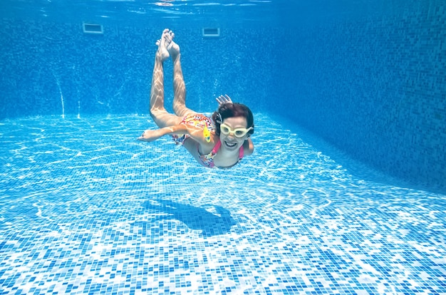 Child swims underwater in swimming pool, little active girl dives and has fun under water