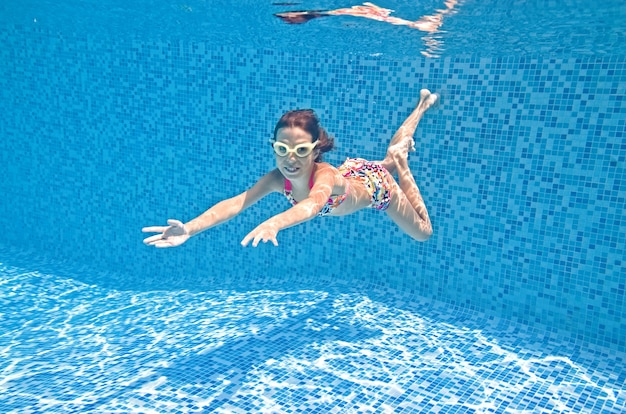 Child swims underwater in swimming pool little active girl dives and has fun under water