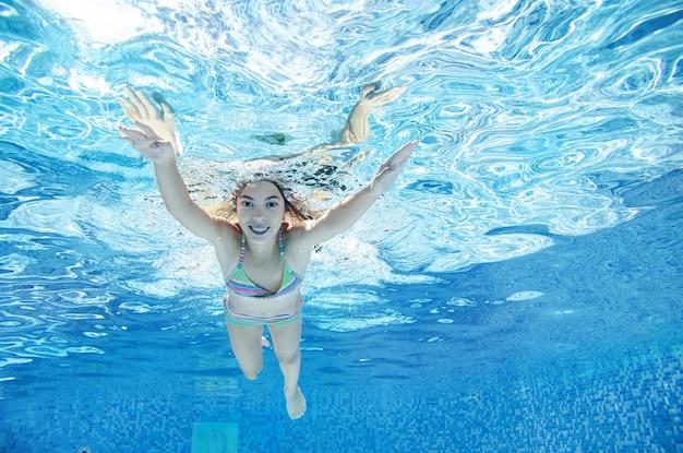 Child swims underwater in swimming pool