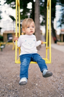 Child swinging on a yellow swing in the playground