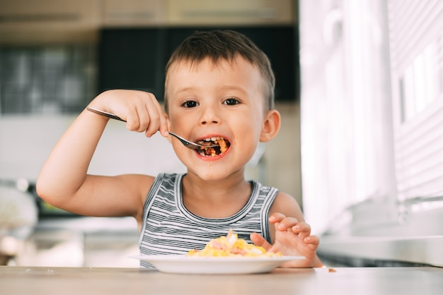 A child in a t-shirt in the kitchen eating an omelet with sausage and tomatoes with a fork