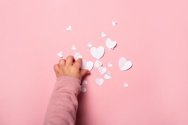 子供はピンクの背景の紙からバレンタインカードを取ります。作曲バレンタインデー。バナー。フラットレイ、上面図。