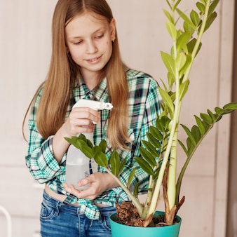 The child takes care of the plants at home, sprinkling the plant with clean water from a bottle.