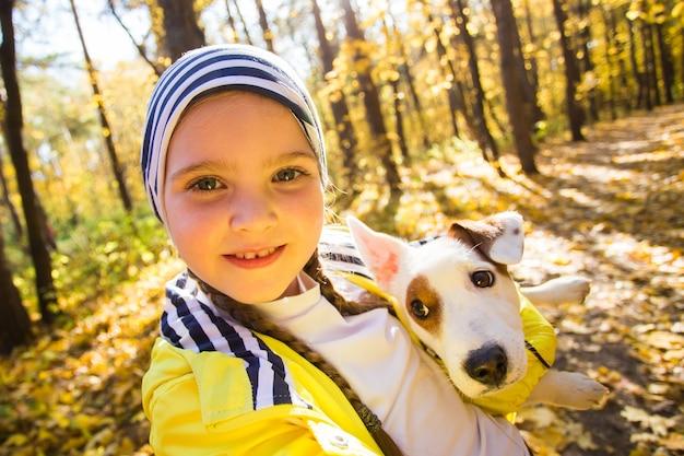 犬のジャックラッセルテリアと一緒に自分撮りをしている子供