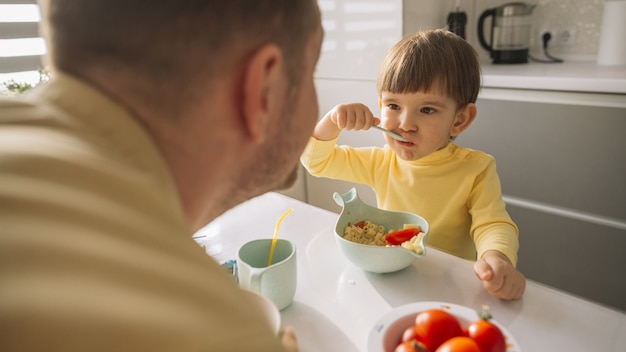 Child taking cereals from the bowl and eats
