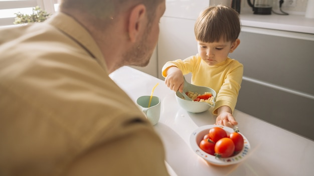 Child taking cereals from the bowl with spoon