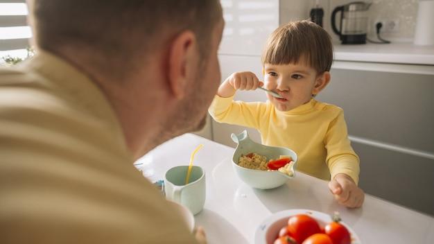 Ребенок берет хлопья из миски и ест