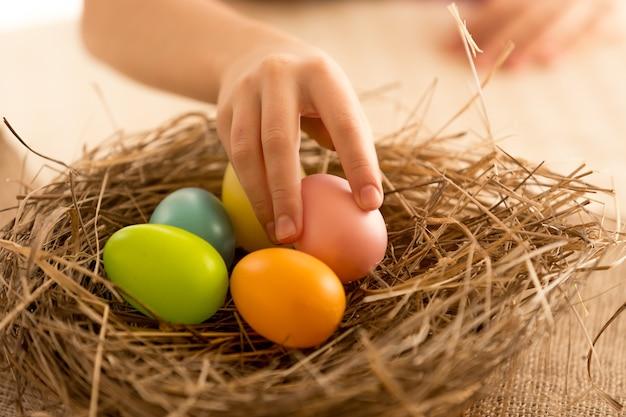 ペイントされたイースターエッグを巣から取る子供