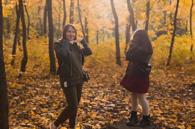 가을 공원 취미와 여가 개념에서 복고풍 카메라로 엄마를 찍는 아이