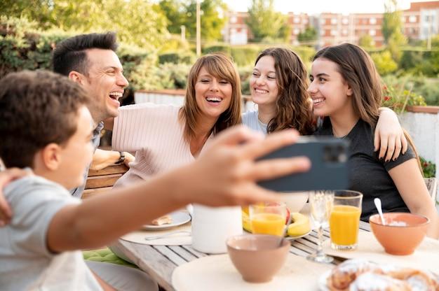 一緒に屋外で昼食をとっている家族のselfieを取る子供