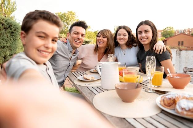 야외에서 함께 점심을 먹는 가족의 셀카를 찍는 아이
