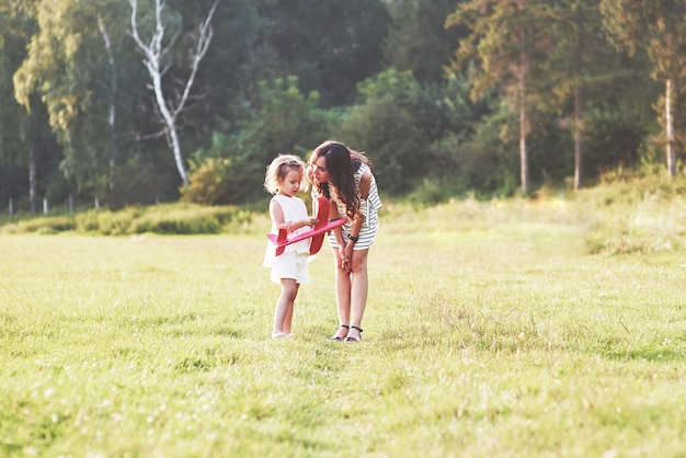 Child talking about the airplane toy in her hands to a mother on the outdoor