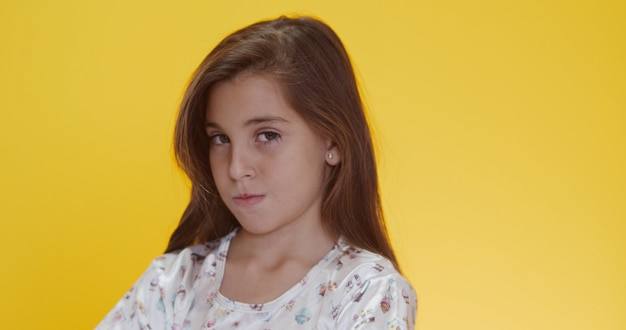 Child tantruming crossing the arms. on yellow background.