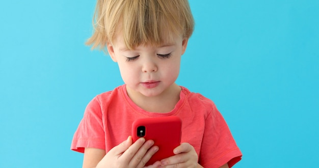 Child tapping cell phone screen, interest in modern technology