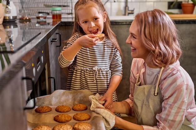 Ребенок пробует печенье, испеченное вместе с мамой, стоит у плиты или плиты. дома, наслаждаясь готовкой