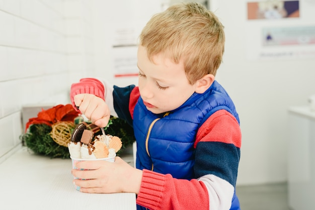 Child tasting an ice cream and eating it with childish cravings.